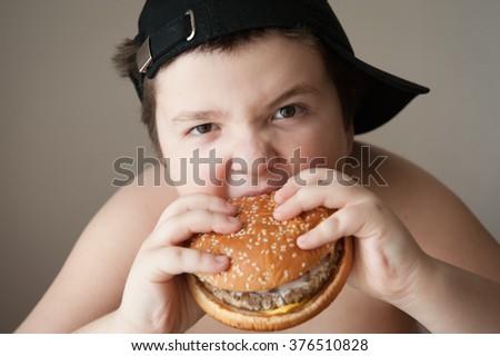fat boy in cap eats a hamburger - stock photo