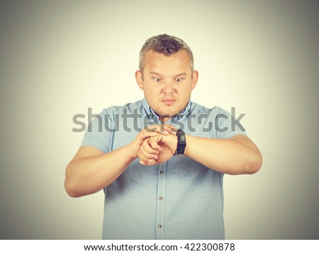 Fat businessman late for work, looking at his watch on isolated on background - stock photo