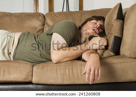 Fat guy sleeping on the couch in what looks like an uncomfortable position - stock photo