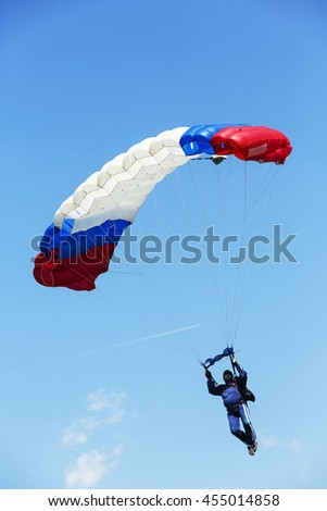 Fat man as Skydiver with parachute on blue sky - stock photo