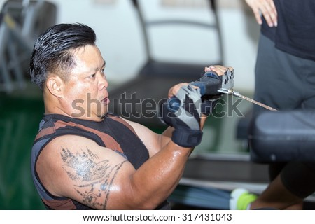 Fat Man Asian Bodybuilding exercises in the gym.