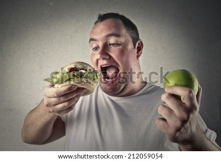 fat man deciding whether to eat a healthy apple or more appetizing junk food - stock photo