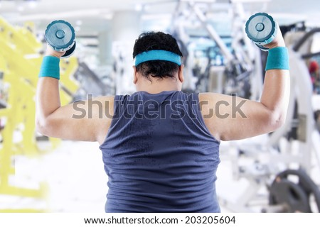 Fat man exercising with two dumbbells in the fitness center - stock photo
