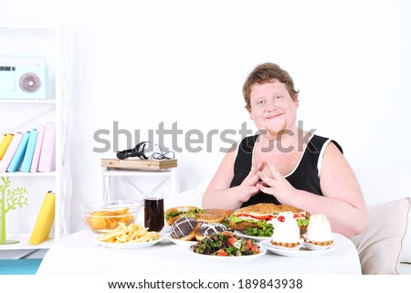 Fat man has a big lunch, on home interior background   - stock photo
