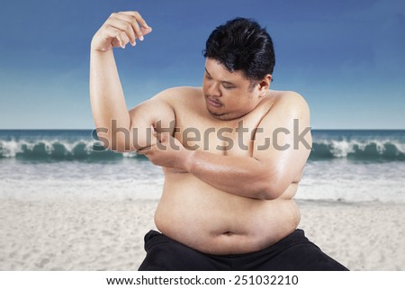 Fat man holding his flabby biceps, shot outdoors at beach - stock photo