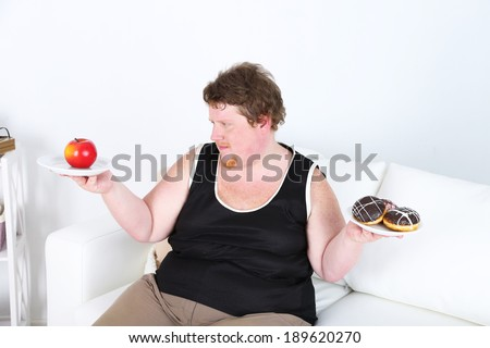 Fat man holding plated with apple and donuts on home interior background.  Choosing between good healthy food and bad unhealthy food   - stock photo