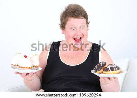 Fat man  holding plates with bad unhealthy food on home interior background   - stock photo