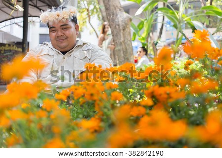 Fat Man in flower wreath. man with wreath of flowers. Fat Man wearing flowers crown and sit behind the orange color flowers field. Selective focus at man. - stock photo
