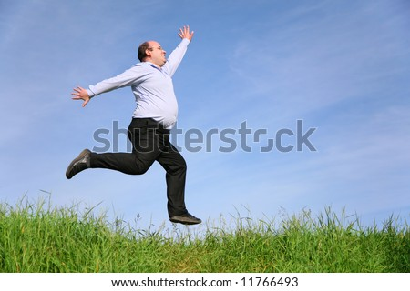 fat man jumps on meadow
