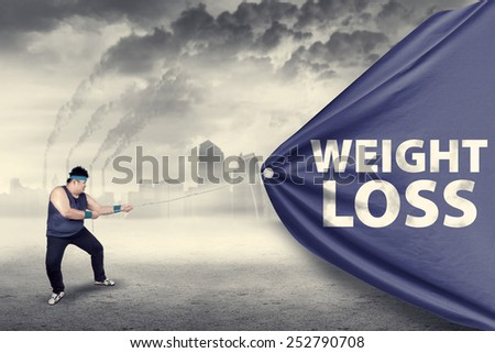 Fat man pulling a weight loss banner, shot outdoors - stock photo