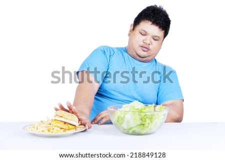 Fat man refuse junk food and choose to eat healthy food - stock photo