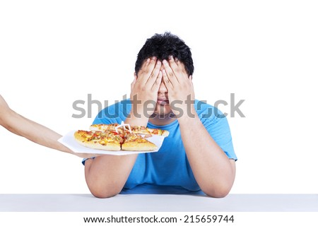 Fat man rejecting to eat junk food. Isolated on white background - stock photo