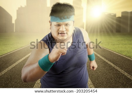 Fat man running for exercising on racing track - stock photo