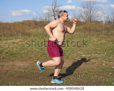 Fat man running outdoors on nature.An active holiday. Fitness, sports. Lifestyle.      - stock photo