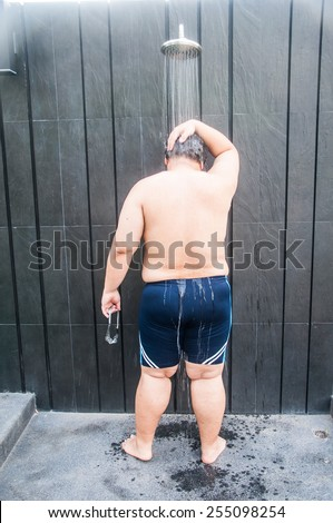 Fat man take shower after pool swim - stock photo