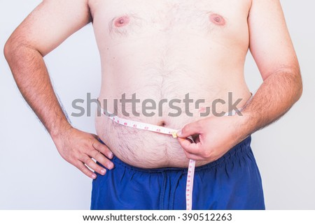 Fat man trying to measure waist circumference
