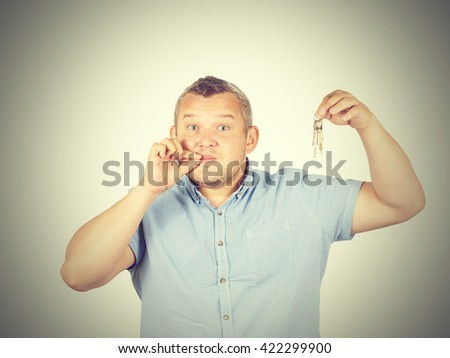 Fat Man with mouth shut holding a keys isolated on background     - stock photo