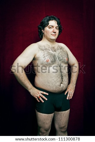 fat proud young man on red background - stock photo