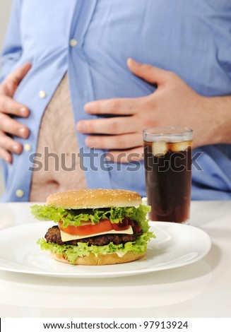 Fat stomach with burger and cola - stock photo