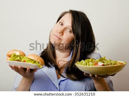 fat white woman having choice between hamburger and salad close up, unhealth fast food - stock photo