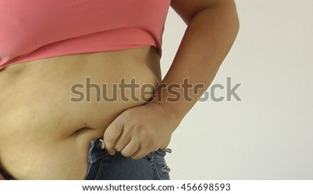 Fat woman body trying to put on her tight jeans