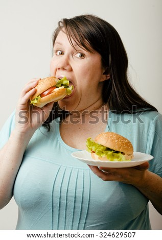 fat woman having choice between hamburger and salad close up emotional