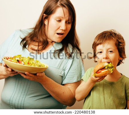 fat woman holding salad and little cute boy with hamburger on white background - stock photo
