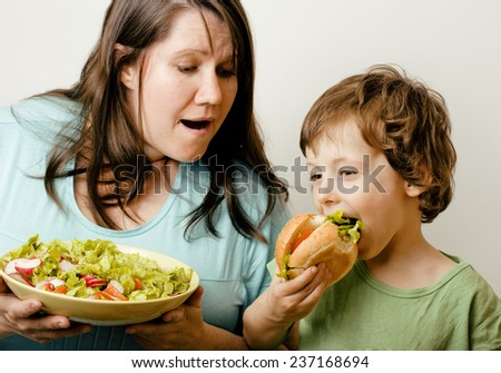 fat woman holding salad and little cute boy with hamburger teasing, real family