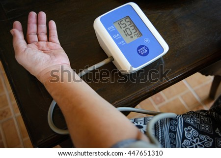 Fat woman is measuring  hypertension blood pressure with herself