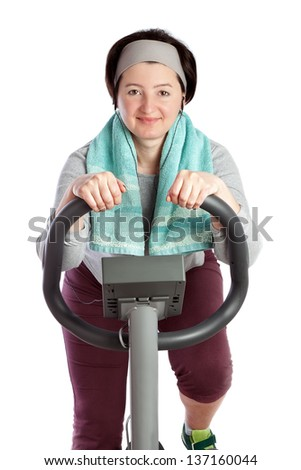 Fat woman loses weight herding fat on a stationary bike. On a white background. - stock photo