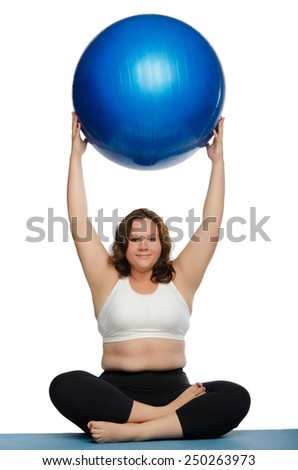 fat woman practicing yoga with blue ball on mat