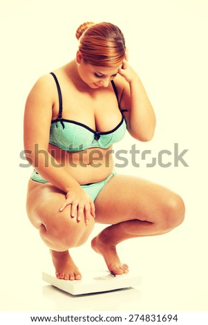 Fat woman squats on scale. - stock photo