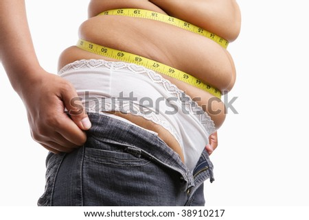 Fat woman trying to wear tight jeans from side with measuring tape around her belly - stock photo