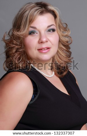 Fat woman with beautiful hair and make-up in a black dress on gray background on Beauty and Fashion