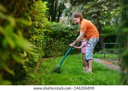 Father and a child cutting the grass with a lawn trimmer