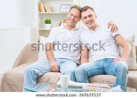 Father and adult son sitting on the sofa