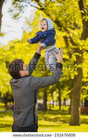 father and baby are playing in the park