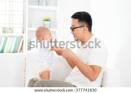 Father and baby boy playing at home. Southeast Asian family lifestyle indoors.