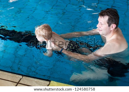 Father and baby boy swimming in a swimming pool indoor - stock photo