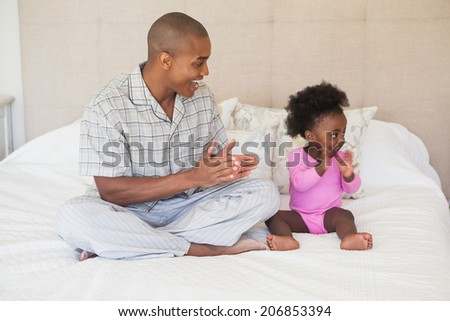 Father and baby girl sitting on bed together at home in the bedroom - stock photo
