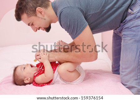 Father and baby in bedroom. He put a pacifier in her mouth. - stock photo