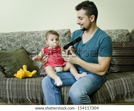 Father and baby in home bedroom watchching TV - stock photo