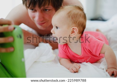 father and baby looking into the tablet computer(digital mobile) in the bedroom. They are chatting with the relatives. The baby is very curious. - stock photo