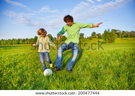 Father and boy playing football together in park - stock photo