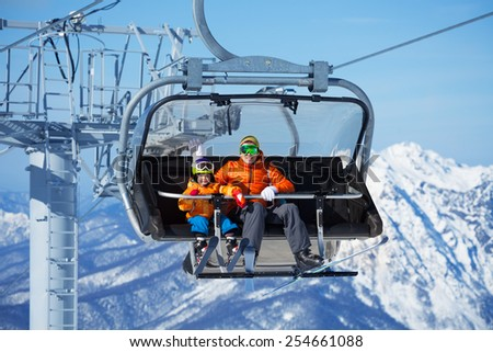 Father and boy sit in ski lift over mountains - stock photo
