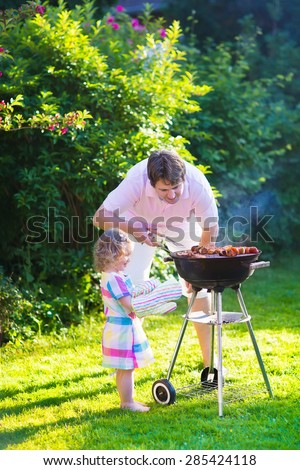 Father and child grilling meat. Family camping and enjoying BBQ. Dad and daughter at barbecue preparing steaks and sausages. Parents and kids eating grill meal outdoors. Garden fun for children.  - stock photo