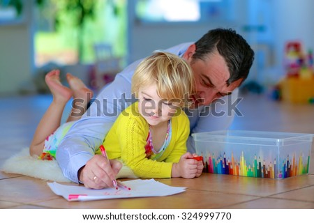 Father and child having quality family time together at home. Happy loving caring dad with adorable toddler girl lying cozy on tiles floor on warm lambskin drawing with colorful felt-tip pencils - stock photo