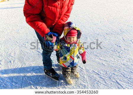 father and child learning to skate in winter snow - stock photo