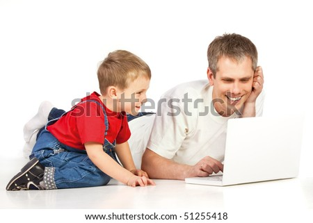 Father and child lying on the floor with laptop