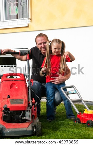 Father and Child mowing the lawn together, daughter has a wheelbarrow and helps daddy getting rid of the lop